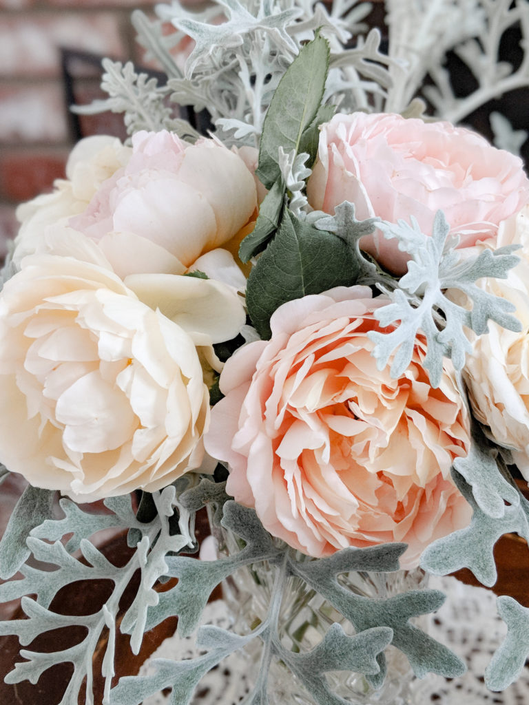 A vase filled with pink, peach, and cream roses, the results of my successful rose-growing adventures.
