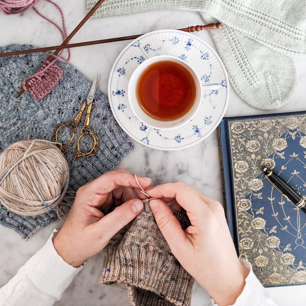 A pair of white hands works on a hat knit with light brown yarn speckled with pink and blue. They are surrounded by other knit items, a teacup filled with tea, a journal with a gilded cover, and ornate scissors. This beginner's guide to knitting will help you get started on your knitting journey.
