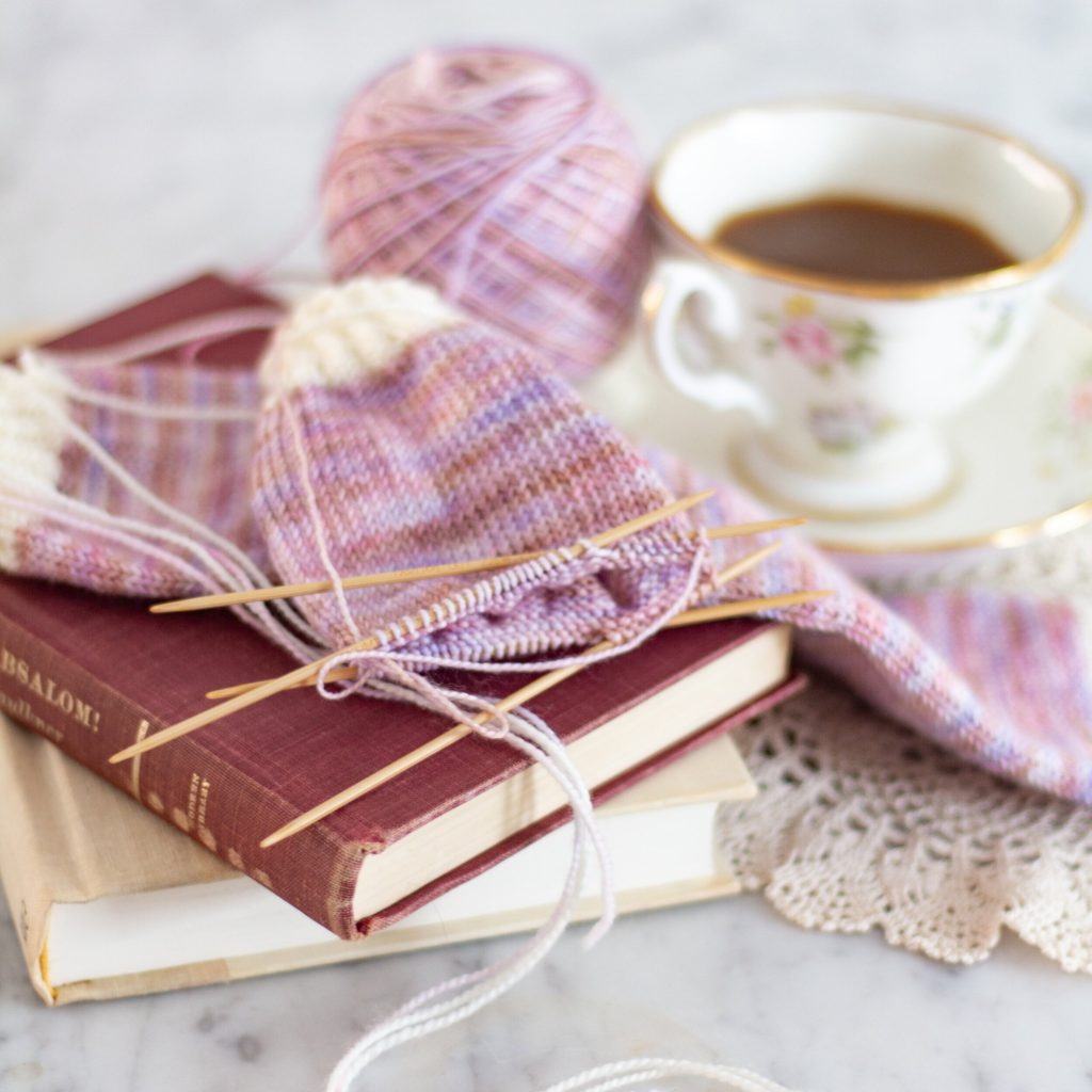 A partially-finished pair of variegated pink and white socks sit on top of a small stack of books. A teacup is slightly blurred in the background. Yarn substitution helped me learn how to use different yarn for socks, sweaters, hats, and more.