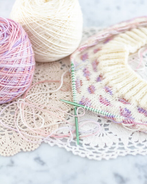 A stranded colorwork cowl in white and variegated pink-purple is laid flat on a white marble countertop. Test knitting helps me ensure these knit projects turn out smoothly.