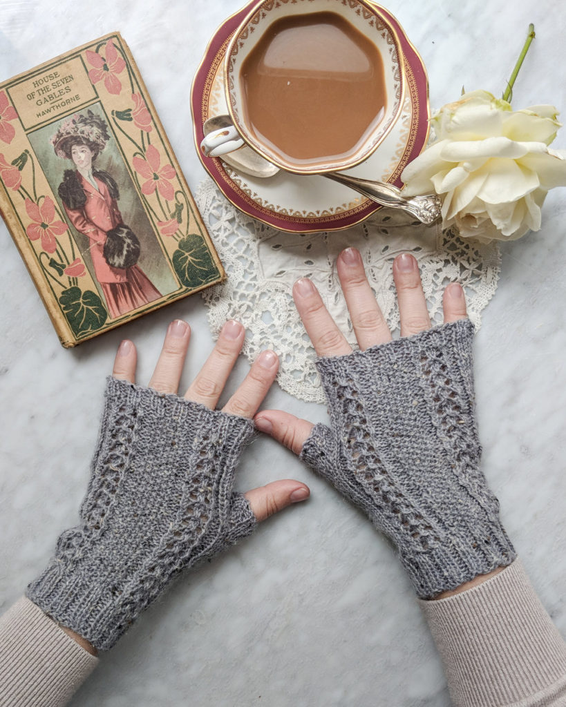A pair of small hands wearing gray, fingerless mitts are splayed out on a white marble countertop with an antique book, a teacup, and a white rose.
