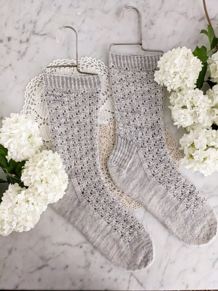 A pair of light gray-blue socks with delicate spiraling eyelets is flat on a white marble countertop with two doilies and several petite white hydrangeas. This free sock knitting pattern will always bee available so long as this website is up and running.