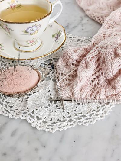 A pink, lacy sweater sleeve on steel needles is laid out on a white marble countertop with an antique pincushion and a white teacup filled with chamomile tea. Test knitting helps me figure out whether details, like lace patterns in my designs, line up in a way that makes sense for knitters.