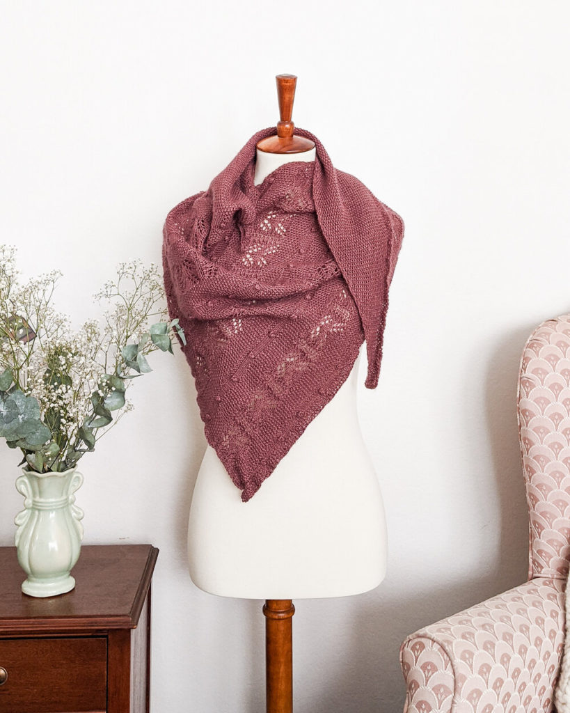 The Berry Scone Shawl, an asymmetrical triangle with stripes of lace, bobbles, and seed stitch, is draped around a white dressmaker's form. It's knit up in a desaturated burgundy color that's reminiscent of baked berries.