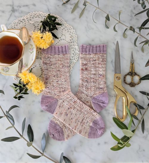 A pair of speckled pink socks with lavender cuff, heel, and toe sits on a white marble countertop with a teacup, yellow flowers, and two pairs of brass scissors. These are the Meringue Socks, the first project my tech editor Bonnie Davis and I worked on together.
