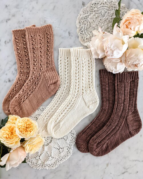Three socks in pink, white, and brown are laid out on a white marble countertop with clusters of peach and yellow roses. These socks represent a triple test knit opportunity.
