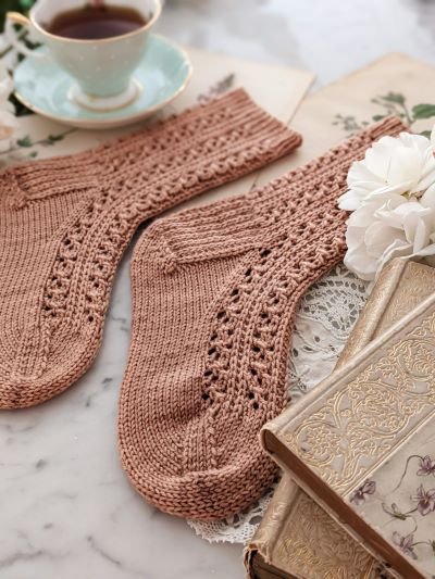 A pair of pink, lacy socks are laid out on a white surface with antique books, white roses, and a pale green teacup. My test knitters helped me get this pattern ready for publication, and I didn't have to impose any strict requirements.