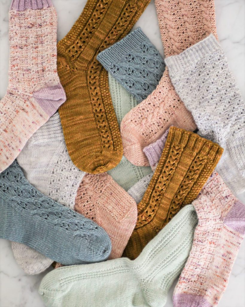 A pile of multi-colored socks in shades of pink, blue, gray, mint, and caramel is tumbled on a white marble countertop. When deciding whether to knit these socks toe-up or cuff-down, there are some important factors to consider.