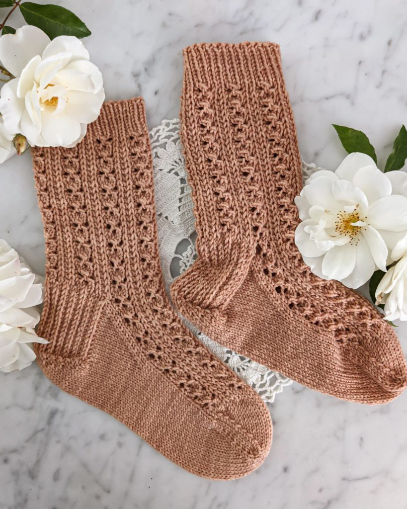 Two knit socks in a clay-colored yarn are laid flat on a white marble counter. One has been blocked and one hasn't.
