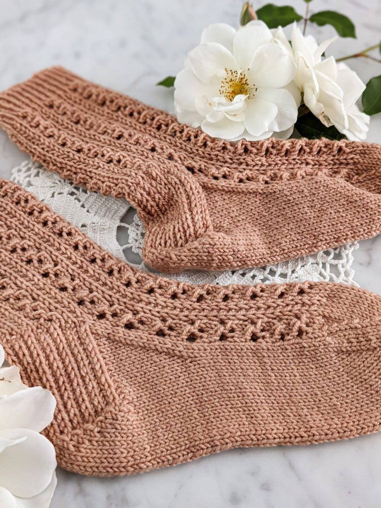 A close-up on the heels of two clay-colored, lacy knit socks. One has been blocked, and therefore sits smooth and flat. The other had not been blocked, and is therefore a bit lumpy.