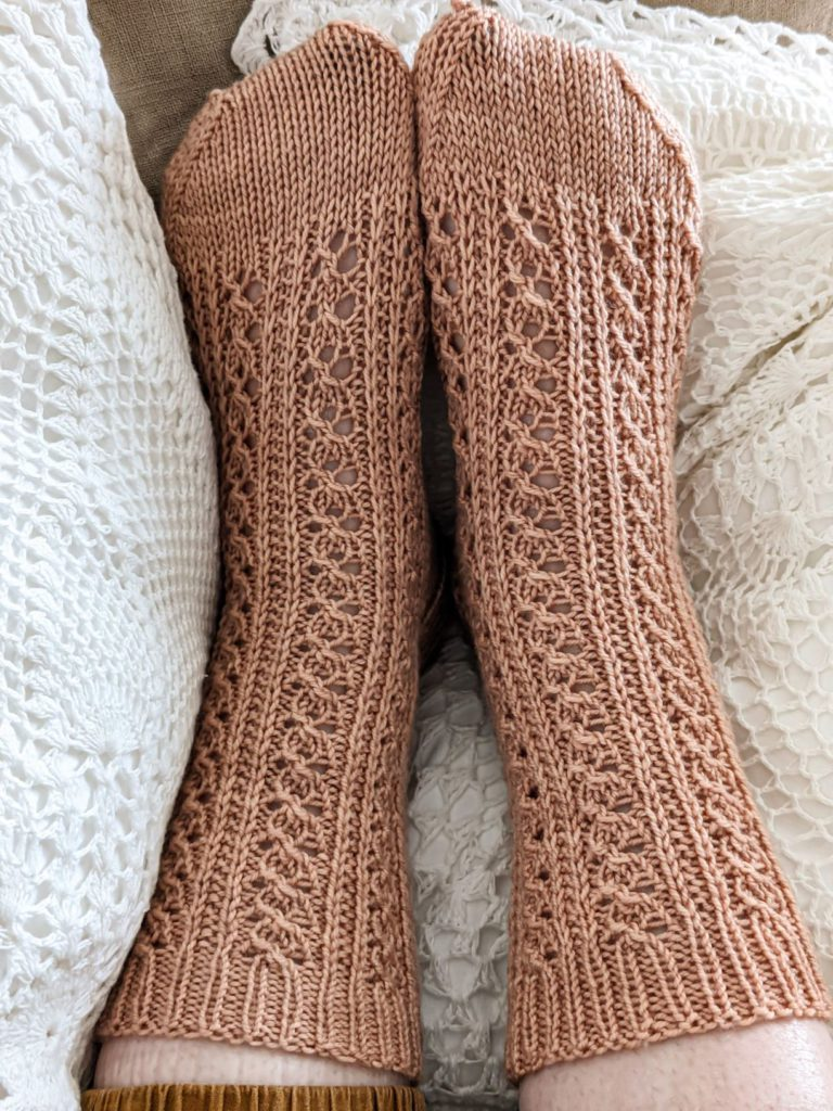 Two lacy, clay-colored knit socks on a pair of feet, resting on white crocheted pillows. The sock on the left sits smoothly on the foot, while the sock on the right is a little wrinkled and puckered.