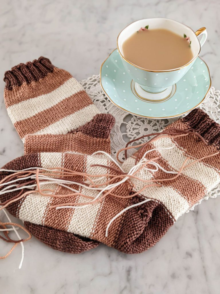 Two handknit striped socks in pink, white, and brown are laid out on a white marble countertop with a mint green teacup and saucer. One sock is turned inside out to show all the loose ends from the stripes. Weaving in ends on knitting projects like this is tedious, but the clasped weft join can help avoid that issue.