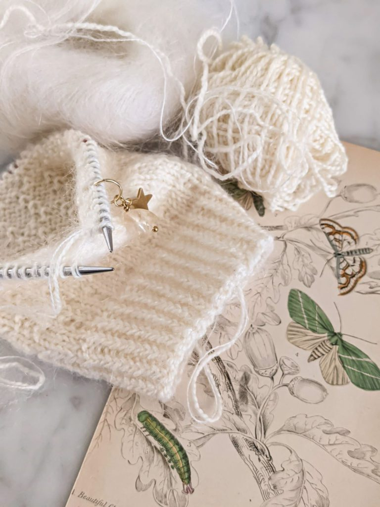 A small, white sock on tiny circular needles is sitting on a white marble countertop with an antique botanical print and two balls of white yarn. These tiny circular needles are some of my favorite needles for knitting socks.