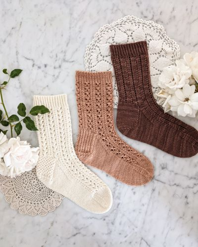 Three lacy socks - one white, one pink, and one brown - are laid flat on a white marble countertop with two doilies and some white roses. These are the Bricolage Socks, the Cromulent Socks, and the Parnassian Socks.