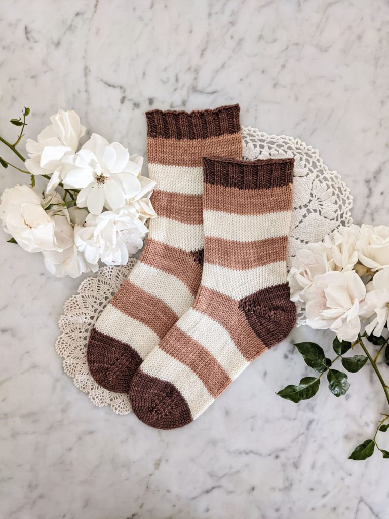 A pair of pink, white, and brown-striped socks are laid flat on a white marble surface with doilies and white roses. I had to experiment to find the right bind-off for my toe-up socks.