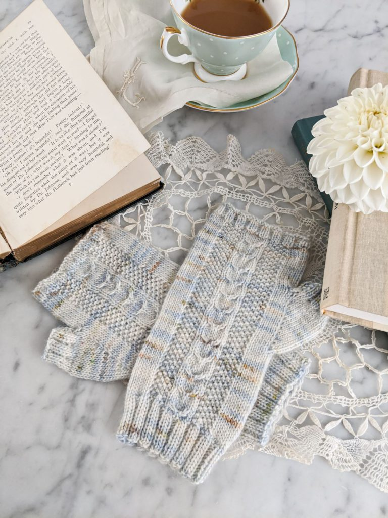A pair of pastel fingerless mitts are laid flat on a white marble countertop, surrounded by books, a teacup, and a dahlia. The small mitts aren't overwhelmed because the larger props have been cropped. This is part of why framing your photograph is so important.