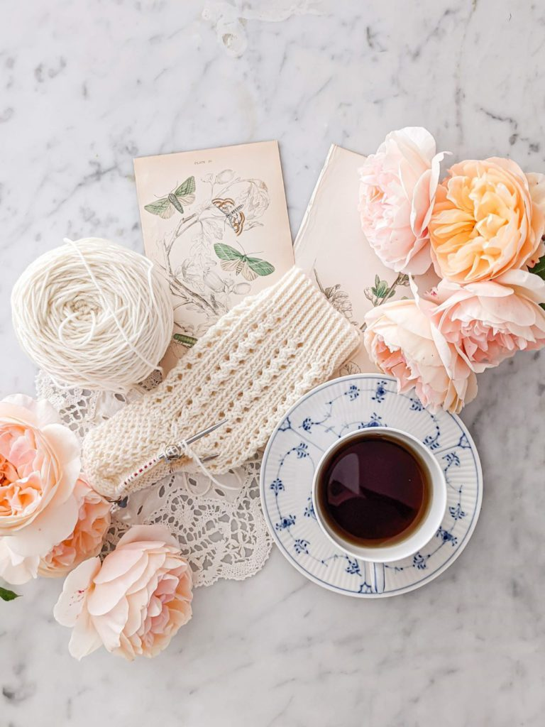 A partially-knit white sock sits on a white marble countertop with antique botanical prints, a doily, peachy-pink roses, and a blue and white coffee cup. There are some simple tricks that can help you take a better flatlay photo in seconds.