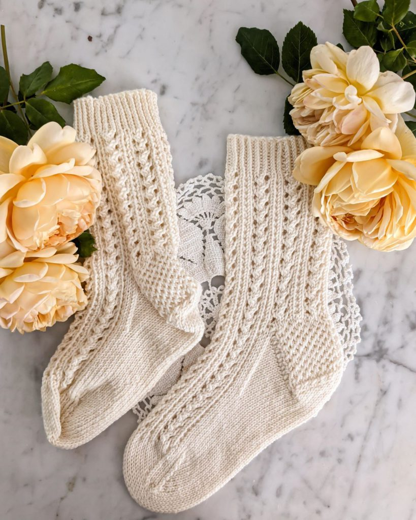 One blocked and one unblocked white sock are laid flat on a white marble countertop with yellow roses in the top corners. The unblocked sock looks lumpy, and shows really strong highlights and shadows. The blocked sock is smooth and the light hits it evenly. Blocking your project is a key step to getting better pictures of your knits.