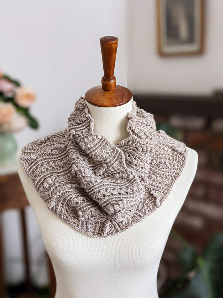 A highly textured gray cowl with lots of bobbles and lace is draped on a white dressmaker's form. Photographing your knits in a vertical space requires different considerations from photographing them on a flat surface.