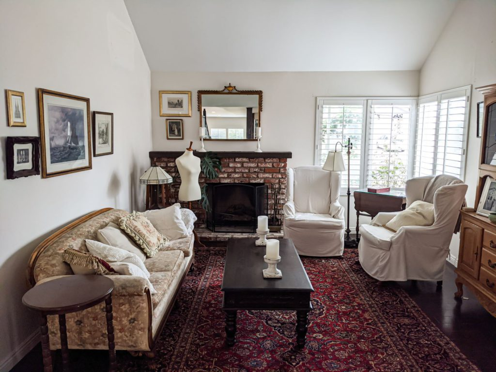 A pulled-out photo of my front room showing a sofa to the left, a brick fireplace on the back wall, two windows in the corners on the right, two slipcovered armchairs, a red Persian rug, and a dark brown coffee table. There is a dressmaker's form in the back left corner, opposite the windows. When photographing your knits, pay attention to where your light sources are.