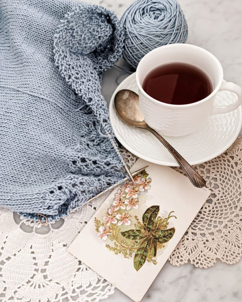 A partially finished, light blue sweater on metal needles is laid flat on a marble countertop next to a white teacup and saucer, some doilies, and an antique postcard with flowers on it. To edit your knitting photos, it helps to know what apps are available and which functions to use.