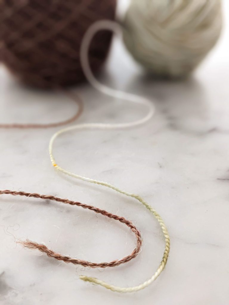 Two strands of yarn are splayed out on a white marble countertop. The yarn on the left, in brown, is woolen spun, resulting in a looser, fluffier yarn. The yarn on the right, in a pale green, is worsted spun, which makes a denser, tighter yarn. Understanding the difference between woolen spun and worsted spun is helpful when making yarn substitutions.