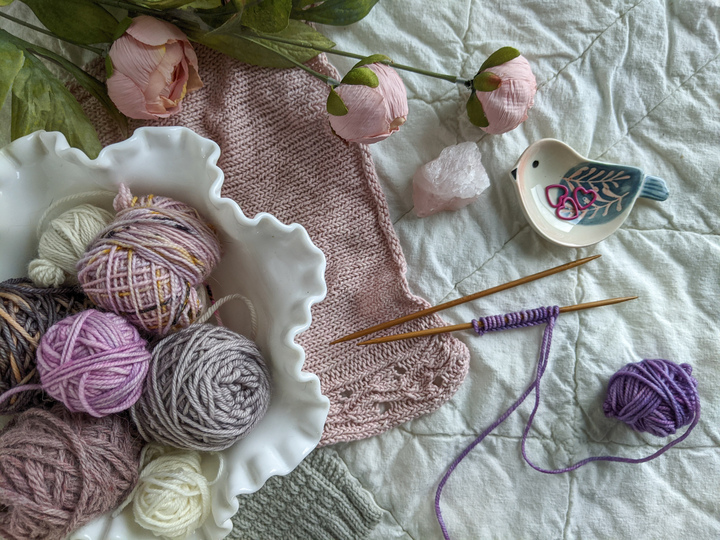 A bowl of soft purple, gray, and cream yarns sits on a white quilt along with a pink knit fabric swatch, some purple yarn on needles, and a little ceramic bird dish with stitch markers in it. When you're substituting yarn in your knit sweaters, swatching is crucial!